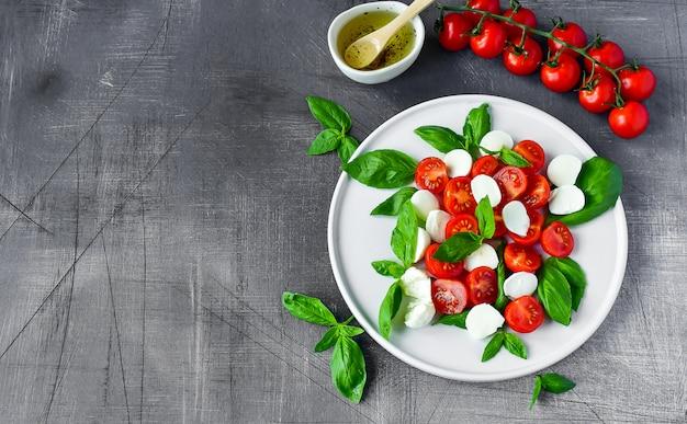 イタリアンカプレーゼサラダ:赤いトマト、モッツァレラチーズとバジル、イタリア料理。ヘルシーなランチ
