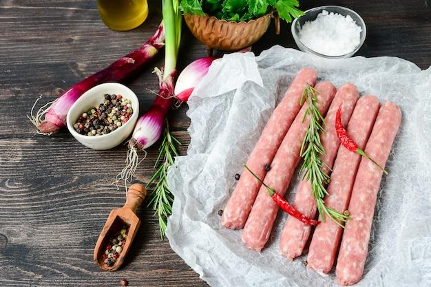 バーベキューやホットドッグ用の生肉ソーセージ。紫玉ねぎ、塩コショウ、マリネ用の新鮮なオレガノ。家族の夕食を焼く
