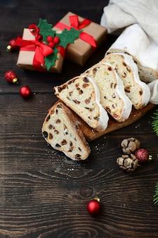 木製のテーブルでスライスされた新年クリスマスデザートシュトーレン。オーストリア料理とドイツ料理のレシピ。ヨーロッパのクリスマス