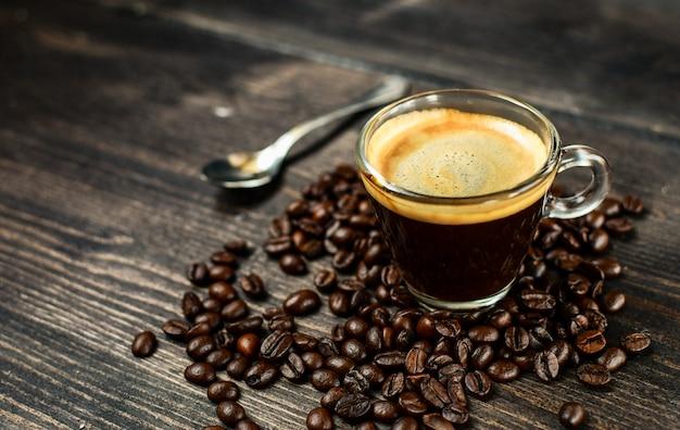 コーヒーカップエスプレッソと木製のテーブルの豆。朝食のコンセプト