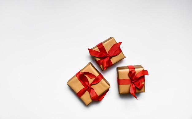 赤の弓とギフトボックス。バレンタインデー、誕生日の記念日、新年とクリスマスのプレゼント。白い背景に分離します。レイアウト