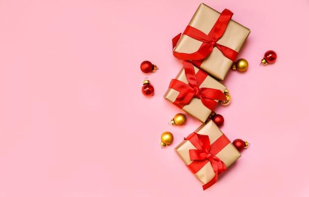 赤い弓、新年とクリスマスのギフトとギフトボックス。ピンクの背景に分離します。レイアウト