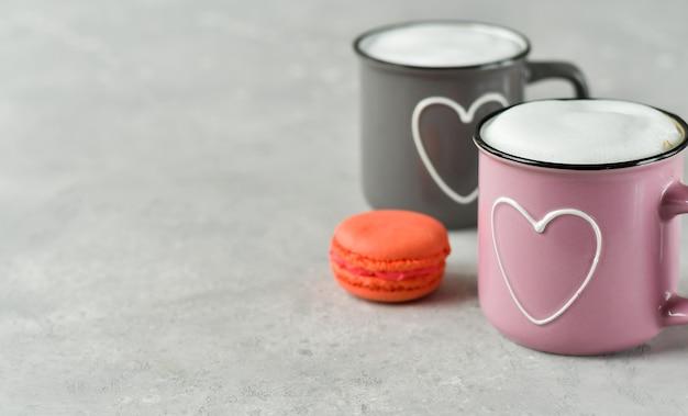 Розовые и серые чашки с капучино и макаронами