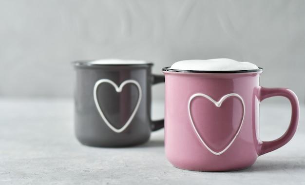 Розовые и серые чашки с капучино