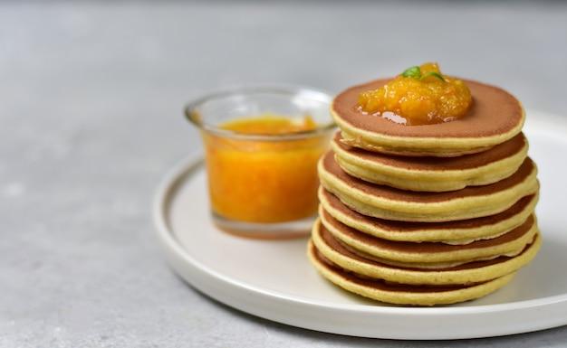 Блинчики с лимонным джемом на белой тарелке
