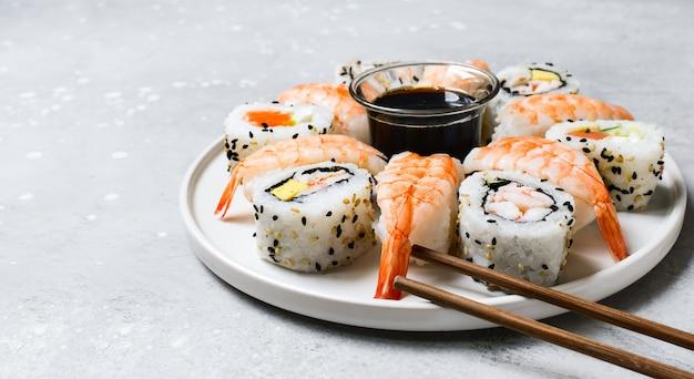 Набор суши и роллы с лососем и креветками на сером столе