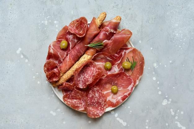 Традиционная итальянская закуска с салями и прошутто на тарелке