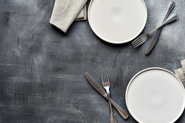 白い皿、カトラリー、暗い石のテーブルにナプキン。テーブルセッティング