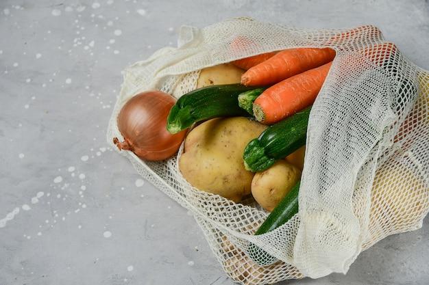 Сетчатая сумка с овощами на сером фоне
