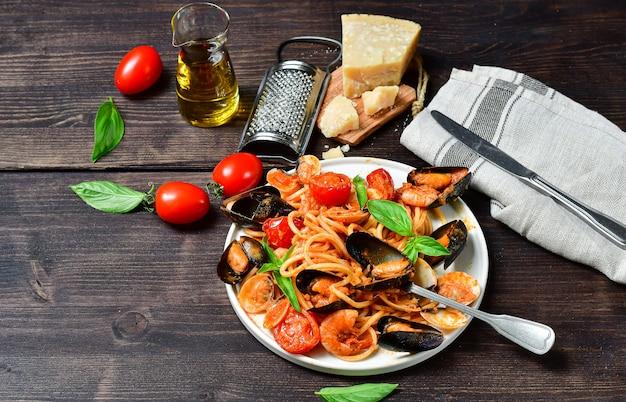 木製のテーブルの上に白いプレートにアサリとムール貝とトマトのエビのスパゲッティシーフードパスタ。イタリア料理のレシピ。上面図