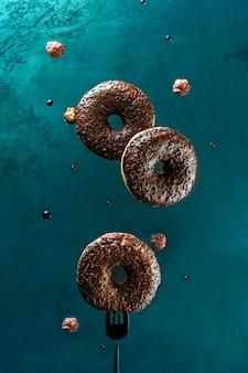 浮上食品。暗い背景にチョコレート艶をかけられた、振りかけたナッツとフライングドーナツ