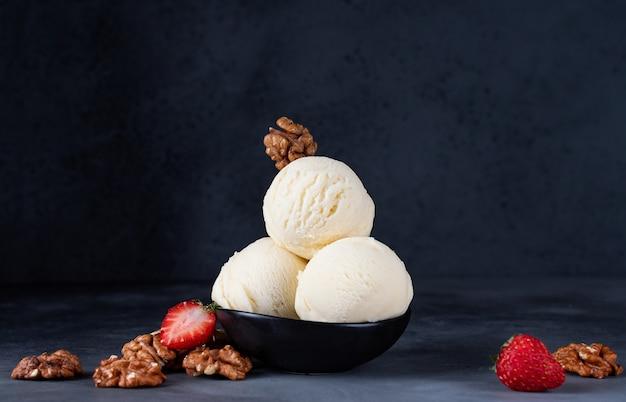 Мороженое три шарика с клубникой и грецкими орехами на темном фоне
