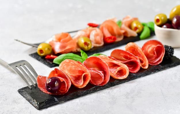 生ハムとサラミ、オリーブのイタリアンレストランの前菜。黒い石の皿で提供しています。