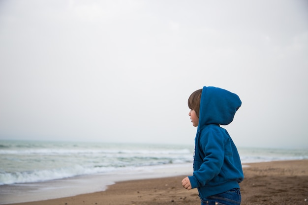海の前でフード付きの小さなブロイ