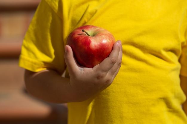 赤いリンゴを持つ子供
