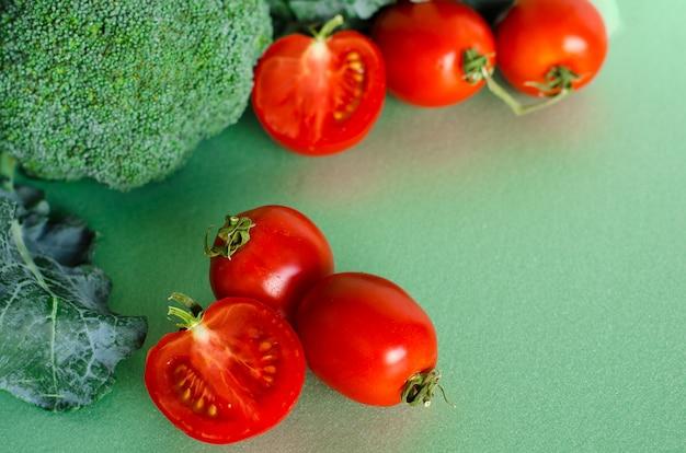 新鮮な生のブロッコリーとトマトの緑の背景とリネン生地。自然食品。