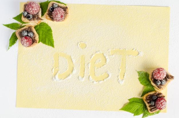 Слово диета написано на сахарной пудре с десертами