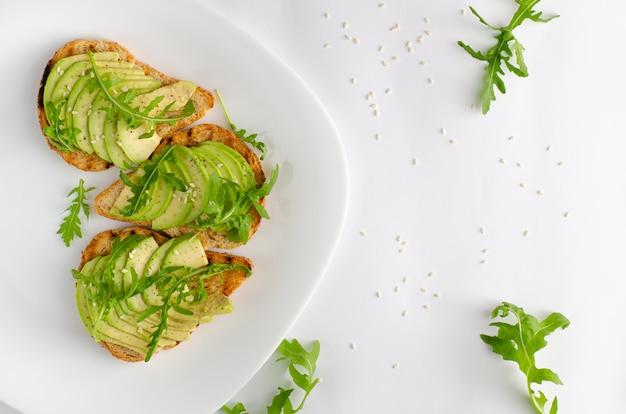 健康食品のコンセプト。白い背景にアボカド、エビ、ルッコラとトースト。トップビュー、フラットレイアウト。