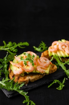 健康的な食事の前菜のコンセプト。ルッコラと黒の背景にエビのアボカドトースト。コピースペース、垂直