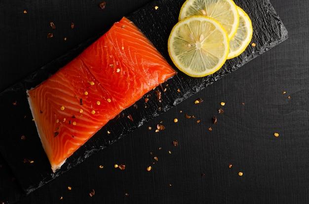 Филе лосося и ломтики лимона на черном