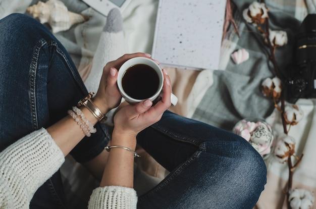 飲み物と白いマグカップを保持している女性の手。ライフスタイルのコンセプトです。上面図