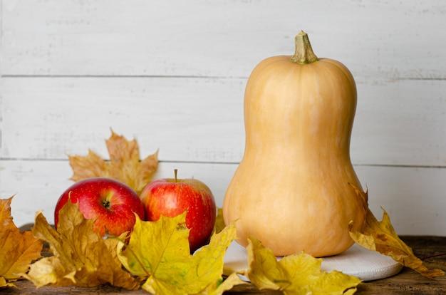 カボチャ、赤いリンゴ、黄色の落ち葉