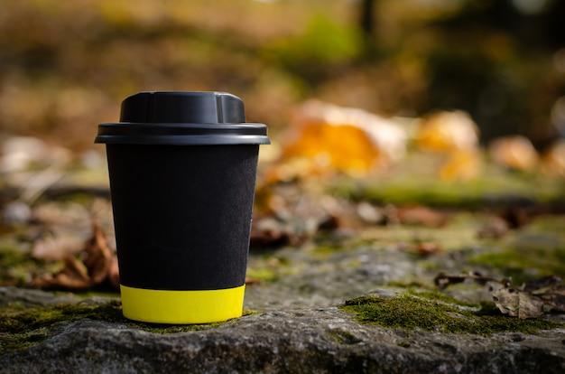落ち葉の背景に屋外に立っている蓋付きのブラックコーヒーカップを奪います。コピースペース、モックアップ