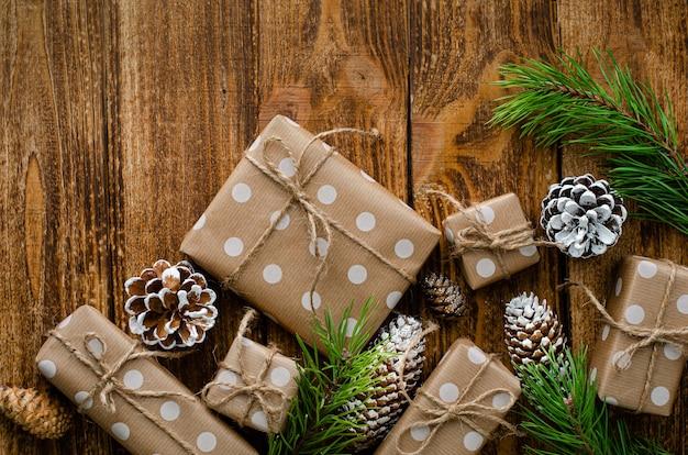 木製の素朴な背景にクラフトペーパー、コーン、モミの枝に包まれたクリスマスギフトボックス。