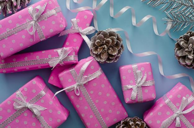 冬の休日の背景。ピンクのギフトボックスとコーン