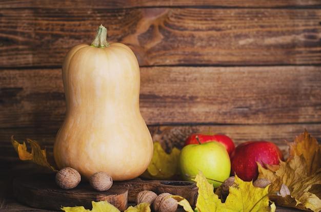 カボチャ、リンゴ、素朴な木製の背景にクルミ