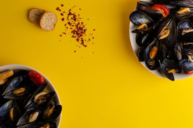 黄色の背景にトマト、唐辛子、ぱりっとしたパンとワインで蒸したムール貝のスープ