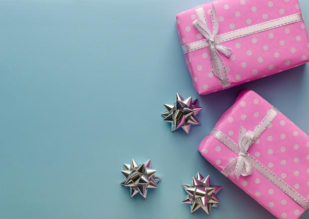 ギフトまたは青の背景にリボン付きプレゼントピンクボックス。バレンタインデーのフラットレイアウト構成