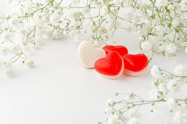 Желейные жевательные конфеты в форме сердца, украшенные цветами на белом фоне