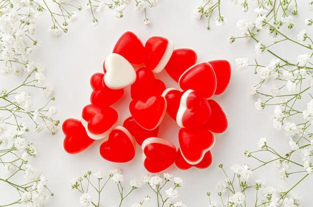 Куча желейных конфет в форме сердца на белом фоне