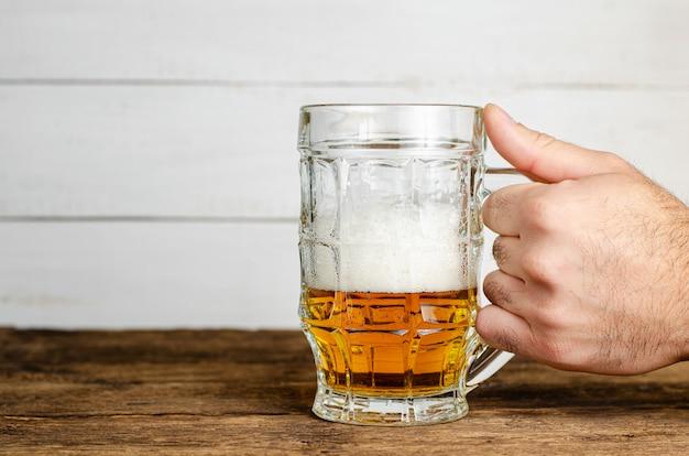 木製テーブルの上の泡と半分フルビールグラスを持っている男性の手