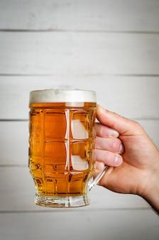 Мужская рука держит кружку пива