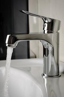 Вода течет из крана или крана в ванной комнате