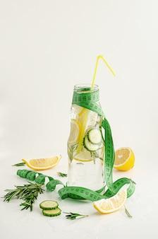 測定テープとレモン、キュウリ、ローズマリーのデトックス水のボトル