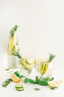 ローズマリー、レモン、キュウリの白い背景の上に健康的なさわやかなデトックス水