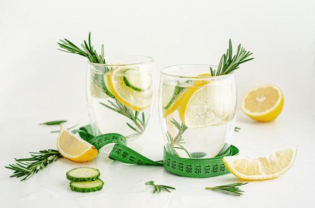 健康的なさわやかなローズマリー、レモン、キュウリの白い背景の上に注入された水