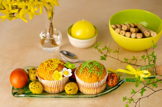 Пасхальные маффины украшены россыпью, цветами мастики, разноцветными перепелиными яйцами
