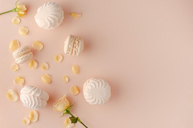 バラの花びら、マカロン、パステル調の背景にメレンゲ