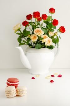 ティーポット、花びら、白い背景の上のマカロンで新鮮なカラフルなバラの花束