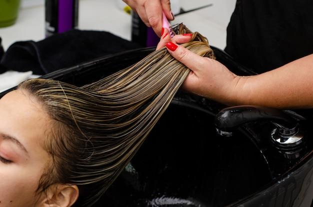 ヘアスタイリストがヘアマスクを適用し、クライアントを黒いシンクのブラシで濡れた髪をとかします。