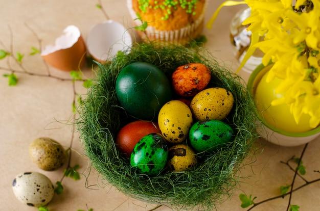 色とりどりの色のウズラのイースターエッグと緑の巣。