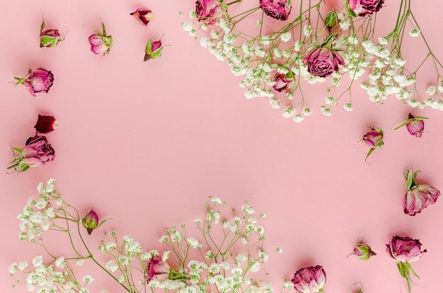 パステルピンクの背景にグリーティングカードの美しい花のフレーム。テキスト用のスペース。平置き