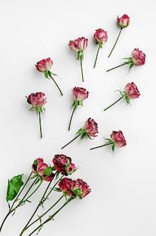 乾燥した赤いバラで作られたヴィンテージの花の背景。フラットレイアウト、オーバーヘッド。