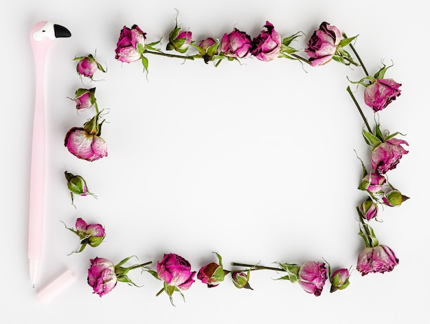 Творческий шаблон или макет. рамка из сухих розовых роз и ручка. вид сверху. копировать пространство