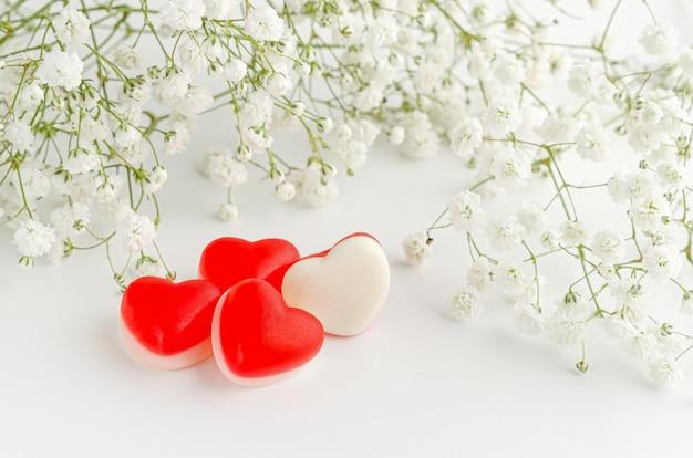 花で飾られたハート型のゼリーのグミ。コピースペース、グリーティングカード、愛の概念