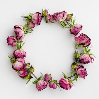 ラウンドフレームまたは白地に乾燥したピンクのバラの花輪。創造的なテンプレートと休日の背景。